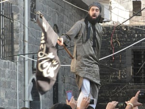 A handout image released by the Syrian opposition's Shaam News Network allegedly shows a Syrian opposition activist waving an black flag of the Islamist Jihadists during a demonstration against the Syrian regime after the Eid al-Fitr prayer in the the central city of Homs on 8 August, 2013.
