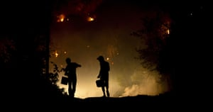 Wildfires in Portugal: Two men carry buckets to try to extinguish a wildfire