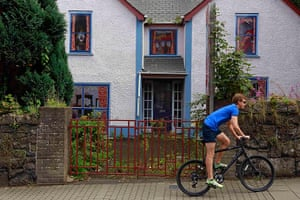 Artworks cover buildings: Boy rides his bicycle past an empty house