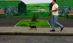 Artworks cover buildings: Man walks his dog past a hoarding