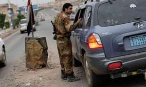 A Yemeni soldier inspects a car at a checkpoint on a street leading to the US embassy in Sana'a