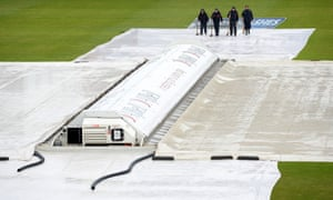 Ground staff clear standing water from the covers at Old Trafford. Play in the Ashes cricket test match between Australia and England is expected to start at 11.30am despite the bad weather forecast