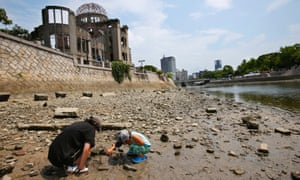 A man and a child search for crabs in the Motoyasu river in front of the Atomic Bomb Dome in Hiroshima, Japan. Tuesday is the 68th anniversary of the US attack on the city in the second world war