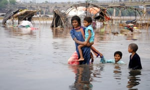 Pakistani children walk in the flooded Ravi river in Lahore. Thunderstorms and heavy rain are forecast across the country, with more flooding expected.