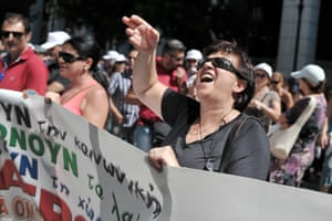 An employee shouts towards the ministry of labour in Athens during a protest march by civil servants on August 5, 2013.