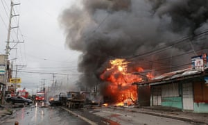 A fire continues to burn following a suspected explosion from a homemade bomb on a main road in Cotabato City, southern Philippines. Six people were killed and 29 were injured in the incident, officials said. The device was believed to be attached to a motorcycle parked on the road.