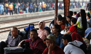 Indonesians sit on the platform at Pasar Senen train station in Jakarta to wait for the trains which will take them back to their home towns to celebrate the Muslim Eid al-Fitr holiday