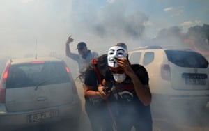 A demonstrator wearing a Guy Fawkes mask runs from tear gas during clashes between Turkish police and protestors. Police are blocking the route to a courthouse in Silivri, Turkey, where the final arguments will be heard in the case against 275 people accused of plotting to overturn the government