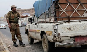 A Yemeni soldier stops a vehicle at a checkpoint in a street leading to the US embassy in Sanaa