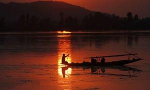 A Kashmiri man rows his Shikara (gondola) on the Dal Lake as sun sets in the backdrop in Srinagar, the summer capital of Indian Kashmir.