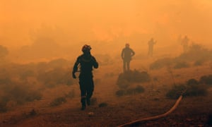 Greek firefighters run to safer ground in Marathon near Athens. A wildfire fanned by strong winds is damaging homes and sending residents fleeing, fire brigade officials said.