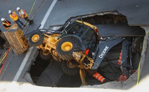 Oh Deere: A construction vehicle lies where it was swallowed by a sinkhole on Saint-Catherine Street in downtown Montreal, Canada. Photograph: Christine Muschi/Reuters