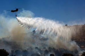 A Greek army helicopter drops water over a forest fire in Marathon near Athens. A wildfire fanned by strong winds raged near Athens, damaging homes and sending residents fleeing, fire brigade officials said. Photograph: Yannis Behrakis/Reuters