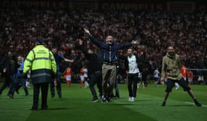 Fans invade the pitch at the final whistle of the Capital One Cup first round match between Preston North End and Blackpool at Deepdale in Preston, England. Photograph: Clive Brunskill/Getty Images