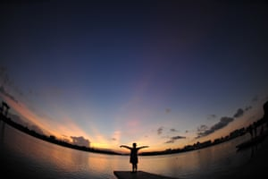 A tourist watches sunset glow by the riverside of Wanquan River in Qionghai City, south China's Hainan Province. Photograph: Meng Zhongde/Xinhua Press/Corbis