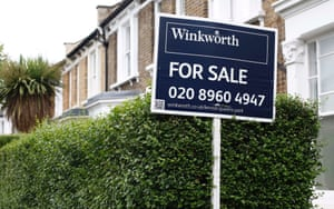 An estate agent's sign is posted outside a terraced house in north London August 2, 2013.
