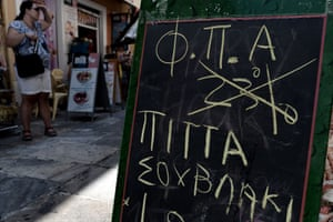 A board with a handwrite announcement of the reduction of the VAT has been placed at a restaurant of Athens on August 1, 2013.