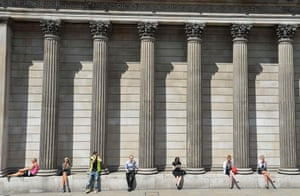 Workers relax during the lunch hour outside the Bank of England in the City of London August 6, 2013.