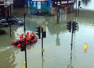 Herne Hill flood: Man trying to get a ride to work on passing rescue boat.