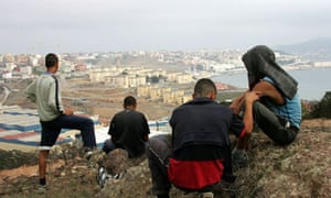 Moroccan youths watch from a hill in the