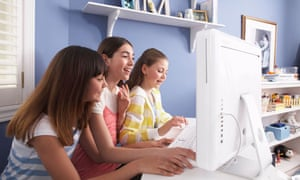 Girls using a computer in a bedroom