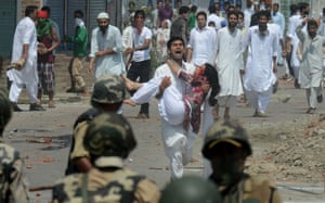 A Kashmiri man carries an injured woman during a clash between protestors and Indian police officials in Srinagar. At least 30 people including 20 police were injured during clashes that broke out after Eid prayers in Srinagar, Indian Kashmir's main city, a police official and witnesses said. Photograph: Tauseef Mustafa/AFP/Getty Images