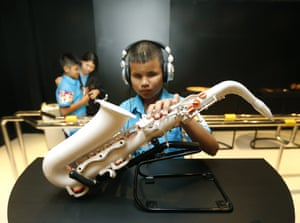 A blind Thai student touches a saxophone on display during the launch of the exhibition for blind at Touch Museum in Siriraj Hospital, Bangkok, Thailand. The Touch Museum opens in honour of Thai Queen Sirikit's birthday on 12 August. Photograph: Narong Sangnak/EPA