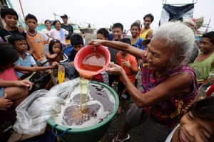 Matilde Margallo, 74, pours diesel they collected in a container which was washed ashore in Rosario town, Cavite province, south of Manila, Philippines. Philippine coast guard dispatched divers to determine the origin of an oil spill that has affected some 300 square kilometres of Manila Bay just outside the capital, a spokesman said. Photograph: Dennis M. Sabangan/EPA