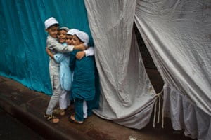 Indian Muslim children hug each other after offering Eid prayers in New Delhi. Eid al-Fitr marks the end of the month of Ramadan, during which Muslims all over the world fast from sunrise to sunset. Photograph: Tsering Topgyal/AP