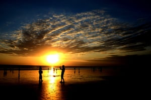 A beautifully silhouetted photo of local people visiting Kuta beach a day after celebrating the Eid al-Fitr holiday in Denpasar on Bali island. Photograph: Sonny Tumbelaka/AFP/Getty Images