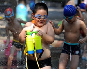 Young boys cool off in a fountain in Hangzhou, capital of east China's Zhejiang Province. Continuous heatwave lingered in the city, with the highest temperature reaching above 41 degrees Celsius . Photograph: Wang Dingchang/Xinhua Press/Corbis