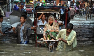 Rickshaw drivers ferry commuters past a waterlogged street after heavy rainfall in Agra, India.