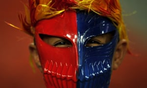 A Barcelona football fan wears a mask during a training session at the Bukit Jalil Stadium on the outskirts of Kuala Lumpur. Spanish club Barcelona is playing a friendly with a Malaysia XI on August 10 as part of the 2013 FC Barcelona Asia Tour.