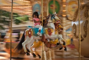 A young girl enjoys a ride on the moving carousel in Pamplona northern Spain. Photograph: Alvaro Barrientos/AP