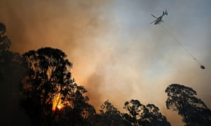 A helicopter carries water to be dropped on a bushfire in Castlereagh, near Sydney.