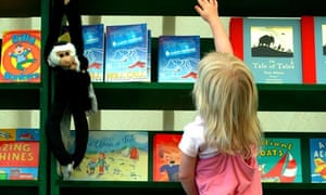 A YOUNG GIRL REACHES UP FOR A BOOK