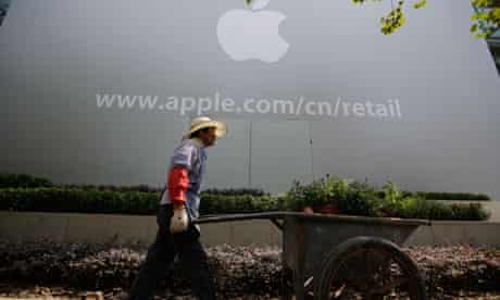 A worker walks in front of an Apple retail shop under construction in Shanghai, China