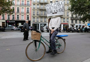 "A man on his bicycle attends a demonstration over pension reforms in Paris, September 10, 2013. French unions take to the streets on Tuesday in protest against a reform of the country's indebted pension system, with some disruption in transport expected but no mass upheaval against an overhaul seen as moderate in scope. The placard reads ""Private and public sector workers, retirement at hundred, no thank you ! ""."