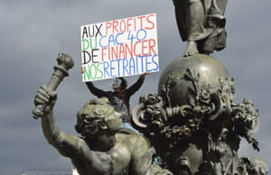 A person holds a placard from the Republic square statue, during a protest against the government's plans to reform France's debt-ridden pension system, on September 10, 2013 in Paris. C