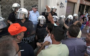 Police stand guard as workers of Greek General Mining and Metallurgical Company (LARCO) shout slogans outside Greece's general accounting office in Athens, Greece, 10 September 2013.