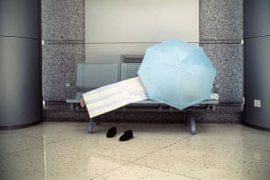 Big Picture - Daydreamers: man lying on bench with blue umbrella covering him