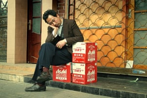Big Picture - Daydreamers: Man sleeping next to crate of beer bottles