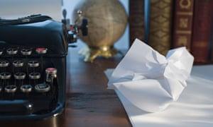 Crumpled writing paper next to a typewriter