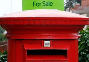 A for sale sign stands behind a post box in Shepshed, central England, September 12, 2013.
