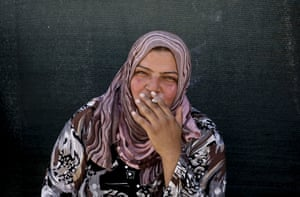 In this Wednesday, Sept. 11, 2013 photo, a Syrian refugee woman smokes a cigarette outside of her tent at a temporary refugee camp, in the eastern Lebanese town of al-Faour in the Bekaa valley, near the border with Syria.
