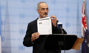 Syrian U.N. Ambassador Bashar Ja'afari shows a document to reporters at the United Nations Headquarters in New York, September 12, 2013.