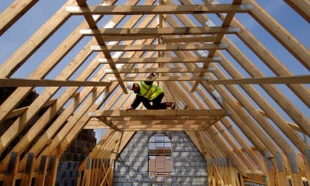 A builder surveying the roof timbers of a new house