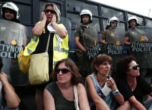 School guards sit in front of the police during a protest outside the Administrative Reforms Ministry in Athens September 16, 2013.