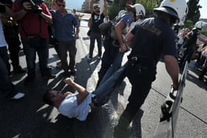 Police drag a school guard on September 16, 2013 outside the Ministry of Administrative Reform in Athens, where hundreds of school guards protestested against their mandatory suspensions