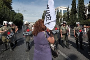 Greek policemen stand opposite a protester as school guards demonstrate outside the Ministry of Administrative Reform in Athens against their mandatory suspensions on September 16, 2013.